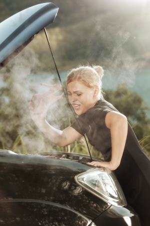 auto leasing: portrait of young beautiful woman with broken car aside