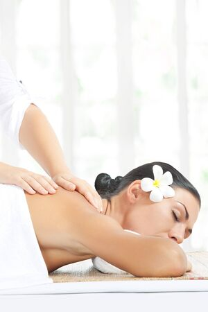 body massage: portrait of young beautiful woman in spa environment
