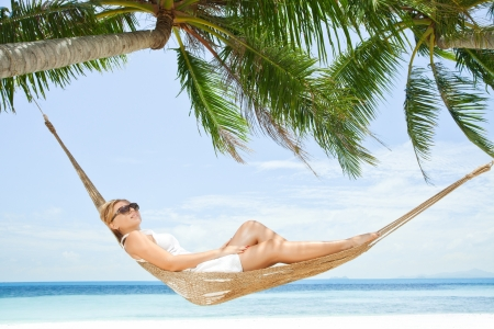 view of nice young lady swinging  in hummock on tropical beach Standard-Bild