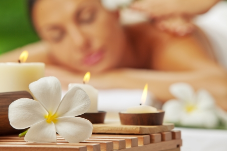 portrait of young beautiful woman in spa environment  blurred face, focused on flower