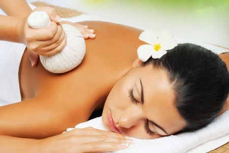 massage herbal: portrait of young beautiful woman in spa environment