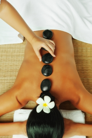 stone therapy: close up view of spa procedure on color  back