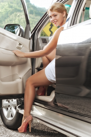 car transmission: portrait of young beautiful woman stepping otta   car