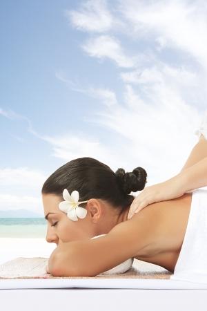 masaje: retrato de la joven y bella mujer en la espalda de color