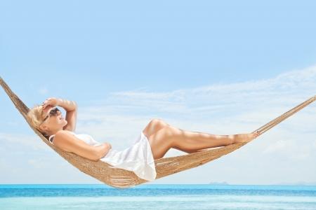 Angesichts der netten jungen Dame schwingt in hummock am tropischen Strand Standard-Bild