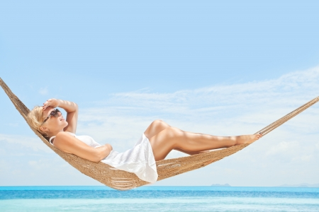 in hammock: view of nice young lady swinging  in hummock on tropical beach Stock Photo