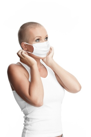 Portrait of nice young woman in surgery mask on white bac
