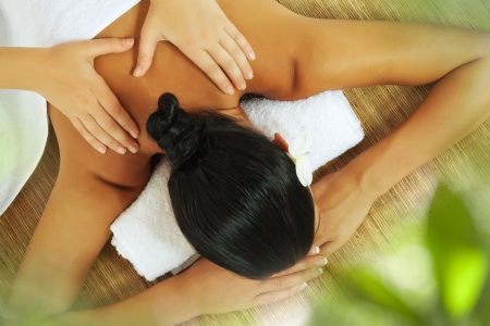 relaxation massage: portrait of young beautiful woman on color back