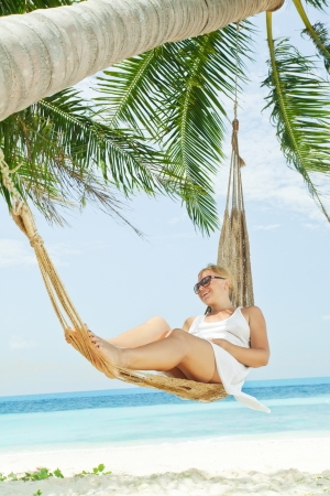 view of nice young lady swinging  in hummock on tropical beach photo