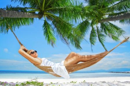 happy holidays: bekijken van mooie jonge dame swingen in hummock op tropisch strand