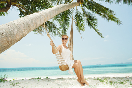 hummock: view of nice young lady swinging  in hummock on tropical beach Stock Photo