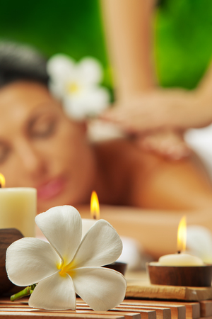 portrait of young beautiful woman in spa environment  focused on candles  photo