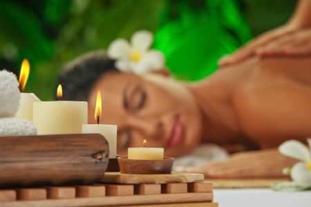 rejuvenate: portrait of young beautiful woman in spa environment  focused on candles  Stock Photo