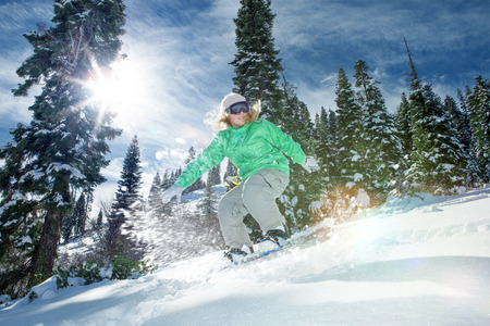 ski slopes: view of a young girl snowboarding in winter environment