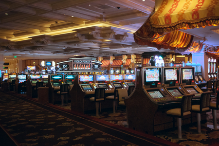 view of nice casino hall with slot machines in dim light
