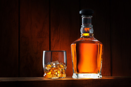 close up view of glass with ice and whiskey and a bottle aside Stock Photo