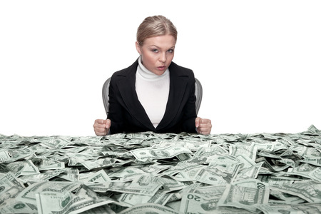 speculation: portrait of young woman sitting behind the table full of cash