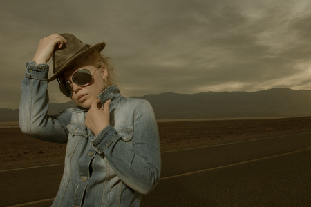 western wear: portrait of young beautiful girl in hat and sunglasses in desert  environment