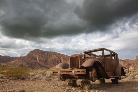 パノラマ ビューの古いアンティークの野生の西環境でさびた自動車