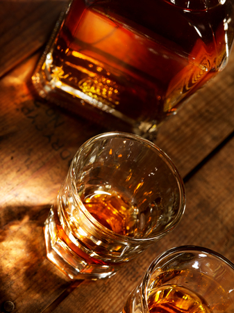 shooter drink: close up view of  nice bottle and two glasses filled with whiskey Stock Photo