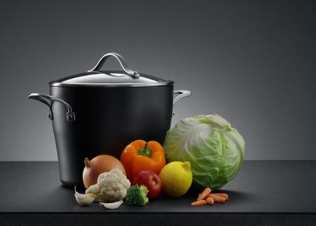utensilios de cocina: Cierre de vista de bonito utensilios de cocina con algunas verduras en el color gris de espalda