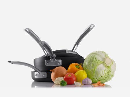 utensilios de cocina: Cierre de vista de bonito juego de ollas con algunas verduras en el color blanco de espalda Foto de archivo