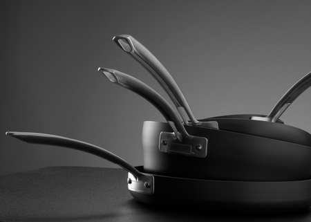 close up view of nice cookware set on grey back Foto de archivo