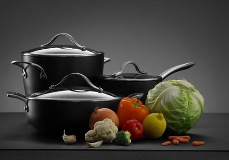 utensilios de cocina: Cierre de vista de bonito juego de ollas con algunas verduras en el color gris de espalda