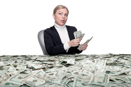 treasurer: portrait of young woman sitting behind the table full of cash