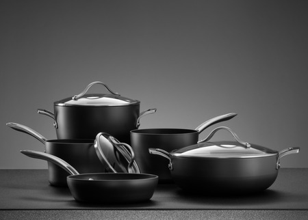 cookware: close up view of nice cookware set on grey color back