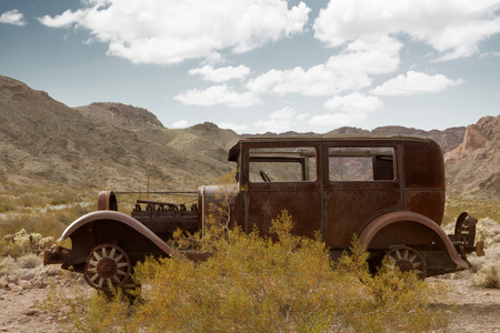 junk car: panoramic view of old antique rusty automobile in wild west environment Stock Photo