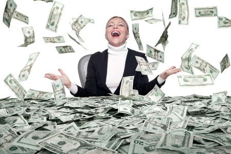 portrait of young woman sitting behind the table full of cash