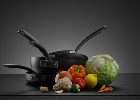 cooking ware: close up view of nice cookware set with some vegetables on grey back