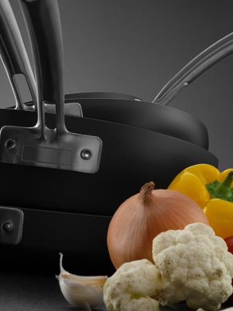 utensilios de cocina: Cierre de vista de bonito juego de ollas con algunas verduras en gris espalda