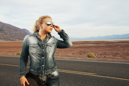 women in jeans: portrait of young beautiful girl is waiting for the car  in desert environment Stock Photo