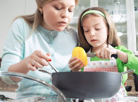 view of young beautiful girl cooking at the kitchen with her mama Stock Photo