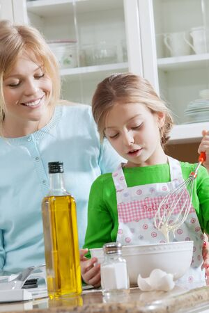 mama: view of young beautiful girl cooking at the kitchen with her mama Stock Photo