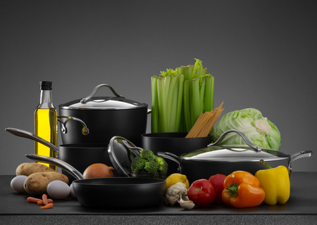 cookware: close up view of nice cookware set with some vegetables on grey back
