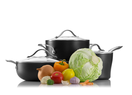 utencilios de cocina: Cierre de vista de las ollas agradables con algunas verduras en la parte posterior del blanco Foto de archivo