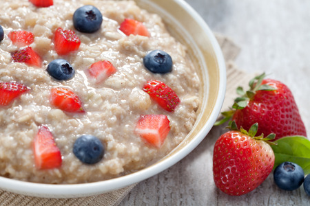 close up view of oatmeal porridge with strawberry on color back