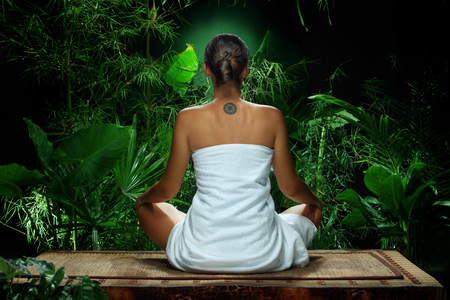 undressed woman: View of nice young woman meditating in spa environment