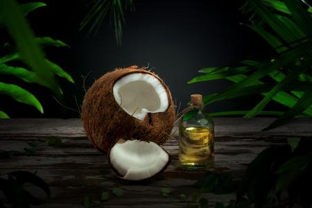aceite de coco: Cierre de vista de agradable fresca de coco y el aceite en el fondo de hoja verde