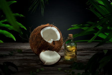 copra: Close up view of nice fresh coconut and oil on green leaf background Stock Photo