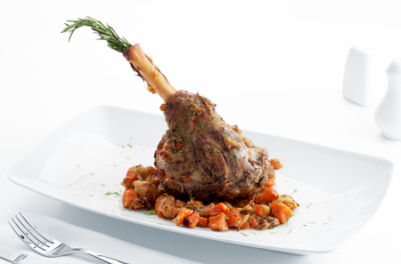 debauchery: Plate with roast leg of lamb, vegetables and rosemary on white back Stock Photo