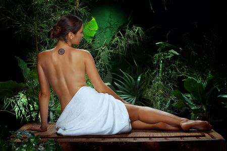 spa beauty: View of nice young woman meditating in spa tropic environment