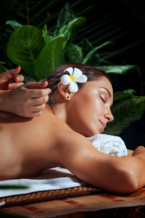 relaxation massage: portrait of young beautiful woman in spa environment