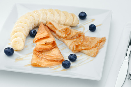 white yummy: close up view of nice yummy crepes with banana on white Stock Photo