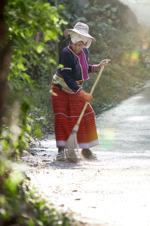 View of thai woman in authentic dress is cleaning street Stock Photo