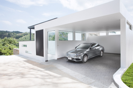 car door: panoramic view of white concrete garage with automobile in it