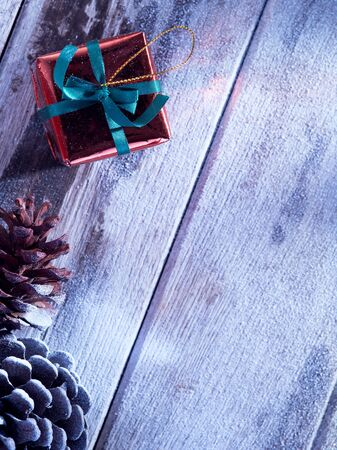snowbound: close up view  of cones and gift box on snowbound  wooden back